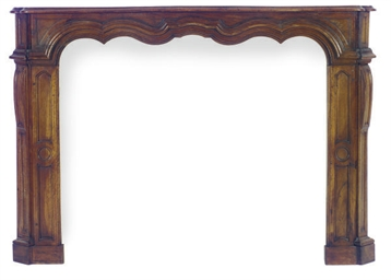 A CARVED WALNUT FIREPLACE SURR