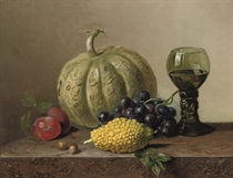 A pumpkin, grapes, prunes and a roemer on a marble ledge