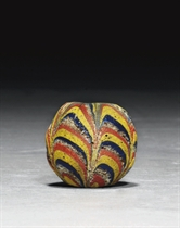 AN EARLY ISLAMIC LARGE MARVERED GLASS BEAD