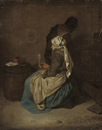 A woman seated holding a glass