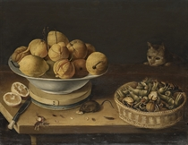 Lemons in a bowl standing on a cheesebox, with a basket of walnuts and hazelnuts, a sliced lemon, a knife and a mouse eating nuts on a wooden table, and a cat