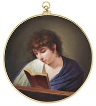 A boy, in open white shirt, purple cloak, reading a book