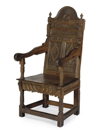 A CARVED OAK WAINSCOT ARMCHAIR
