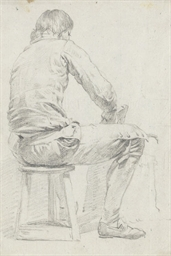 A man sitting on a stool, seen