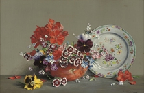 Pansies and other flowers in a bowl, with floral patterned plate to the side
