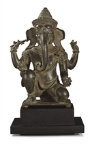 A bronze figure of a kneeling Ganesha