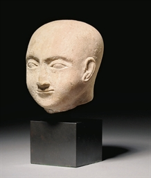 AN EGYPTIAN LIMESTONE HEAD OF