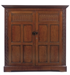 AN OAK PANELLED CUPBOARD