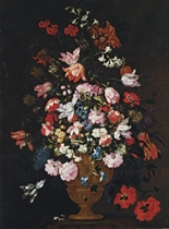 Roses, tulips, lilies and other flowers in a bronze urn on a stone socle