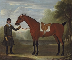 A groom holding a saddled bay