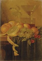 A peeled lemon, an orange, peaches, white grapes and cherries near glassware on a partially draped table