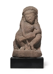 A red sandstone figure of a dr