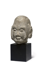 A SMALL LIMESTONE HEAD OF A LU