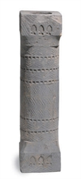 A GREY POTTERY PILLAR,