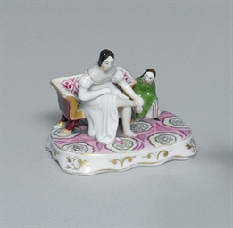 A SMALL PORCELAIN FIGURE OF A
