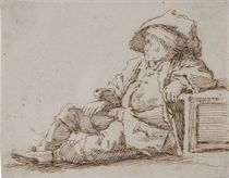 Enfant assis sur le sol, accoudé sur une caisse et portant un chapeau