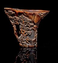 A CARVED RHINOCEROS HORN LIBATION CUP