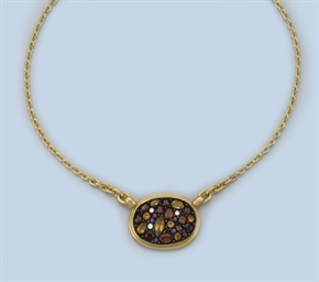 A GEM SET PENDANT ON A CHAIN,