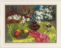 Winter flowers in a vase, with fruit on a plate and a glass of wine to the side, on a table