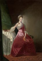Portrait of a lady, full-length, in a red satin dress and silk headdress, seated at a table, a book in her left hand