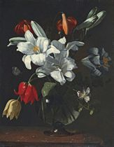 Lilies, tulips and other flowers, in a glass vase, on a ledge
