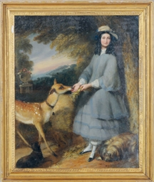 A lady feeding a deer in a for