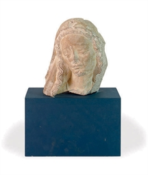 A CARVED LIMESTONE HEAD OF A F