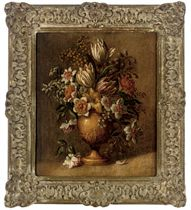 Tulips, mimosa and other flowers in a sculpted urn, on a ledge
