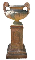 A FRENCH CAST-IRON URN ON PEDE
