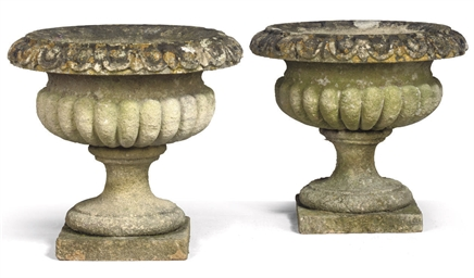 A PAIR OF COTSWOLD STONE URNS