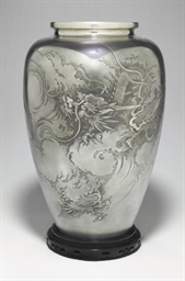 A silver vase with dragon and