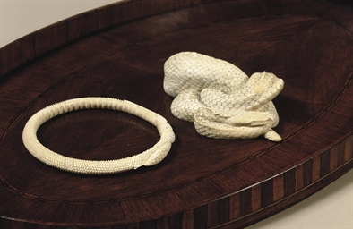 A CARVED IVORY MODEL OF AN ADD