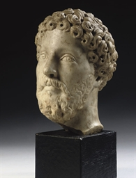 A CARVED MARBLE HEAD OF MARCUS