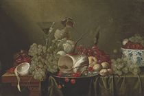 Cherries and a conch shell on a silver platter, a cut and peeled lemon, a pomegranate, grapes, a glass of wine, walnuts and berries in a kraak porcelain bowl, on a partly-draped wooden table