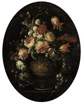 Roses, parrot tulips, carnations and other blooms in an urn on a stone ledge