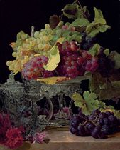 Red and white grapes and silver tableware on a marble ledge