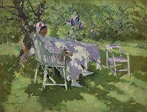 A lady in white seated in a garden