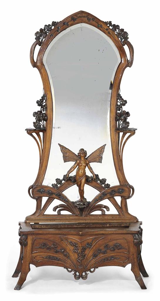 An Art Nouveau Carved Walnut Sculptural Mirror And