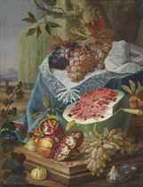 A watermelon, a pomegranate and figs, with grapes on a draped plinth, in a landscape
