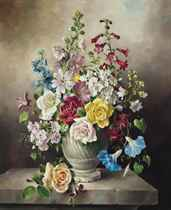 Lavatera, roses, delphiniums, clematis, penstemon and other blooms in a stone urn on top of a pedestal
