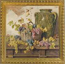 A basket of grapes by an amphor on a wooden table