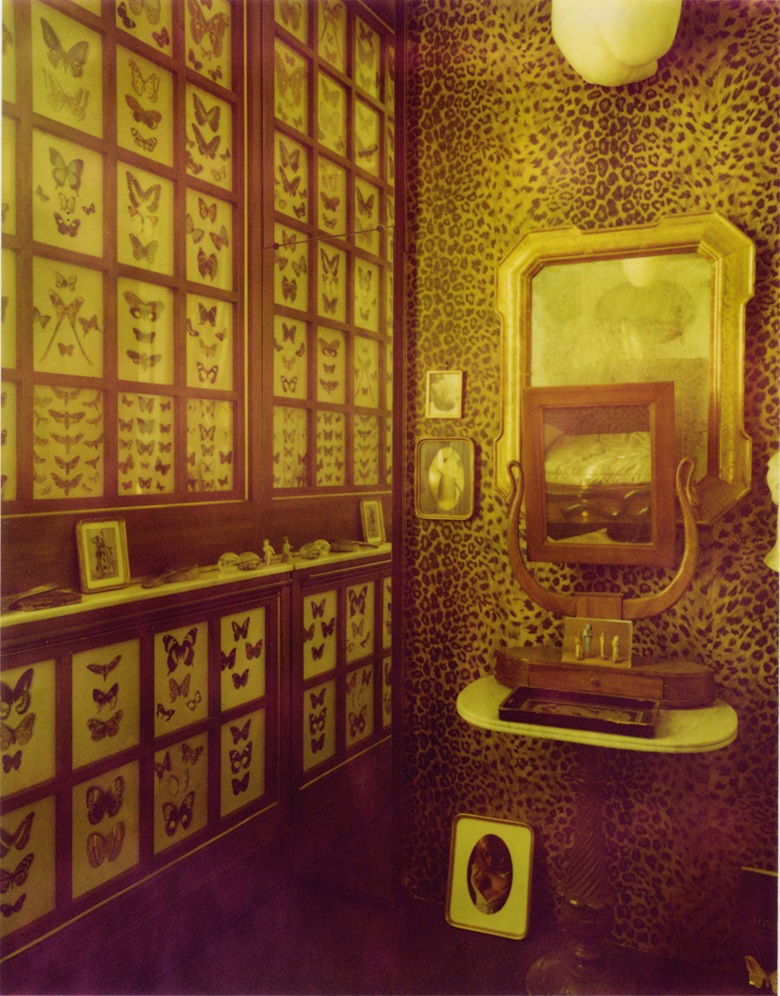 The bedroom, with its leopard-skin wall covering and collection of framed butterflies
