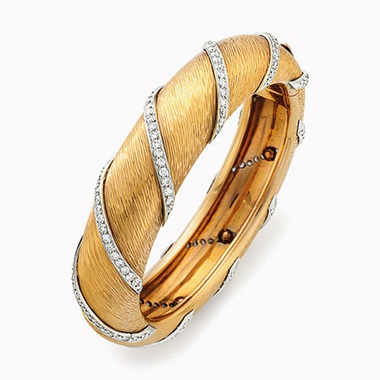 A gold and diamond bangle bracelet, by Bulgari. The hinged bangle designed as a textured 18k-gold bracelet, intersected by diagonal platinum and circular-cut diamond rows, diameter 2½ in. Estimate $5,000-7,000. This lot will be offered in The Private Collection of President and Mrs. Ronald Reagan, 21-22 September at Christies in New York