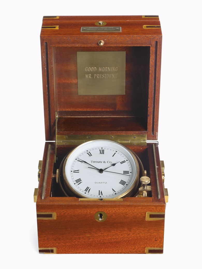 An inaguration gift from Mr. and Mrs. Francis [Frank] Sinatra to President Ronald Reagan, January 20, 1981. An American marine chronometer, by Tiffany, 20th century. The matt silvered dial with Roman numerals, black finished hands, brown bowl, gimballed in brass-bound mahogany box, the hinged lid with a plaque engraved, 'Good Morning Mr. President', and dedication plaque to the front,