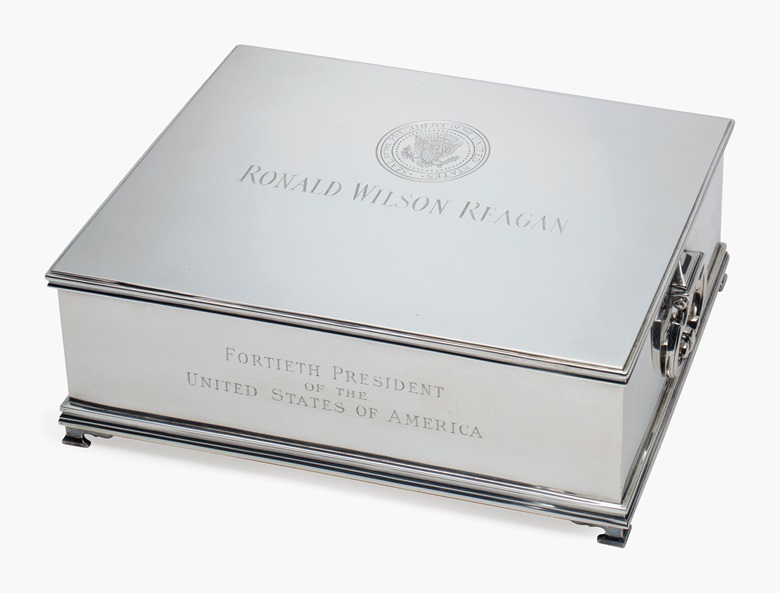 An American silver musical humidor, mark of Tiffany & Co., New York, circa 1981. The hinged top engraved with the Presidential Seal of The United States, 'RONALD WILSON REAGAN, FORTIETH PRESIDENT OF THE UNITED STATES OF AMERICA, WITH PRIDE AND BEST WISHES ALWAYS, BOB GRAY'. Mahogany-lined, playing 'All Hail the Chief', marked to the underside. 3 ½ in (8.3 cm)