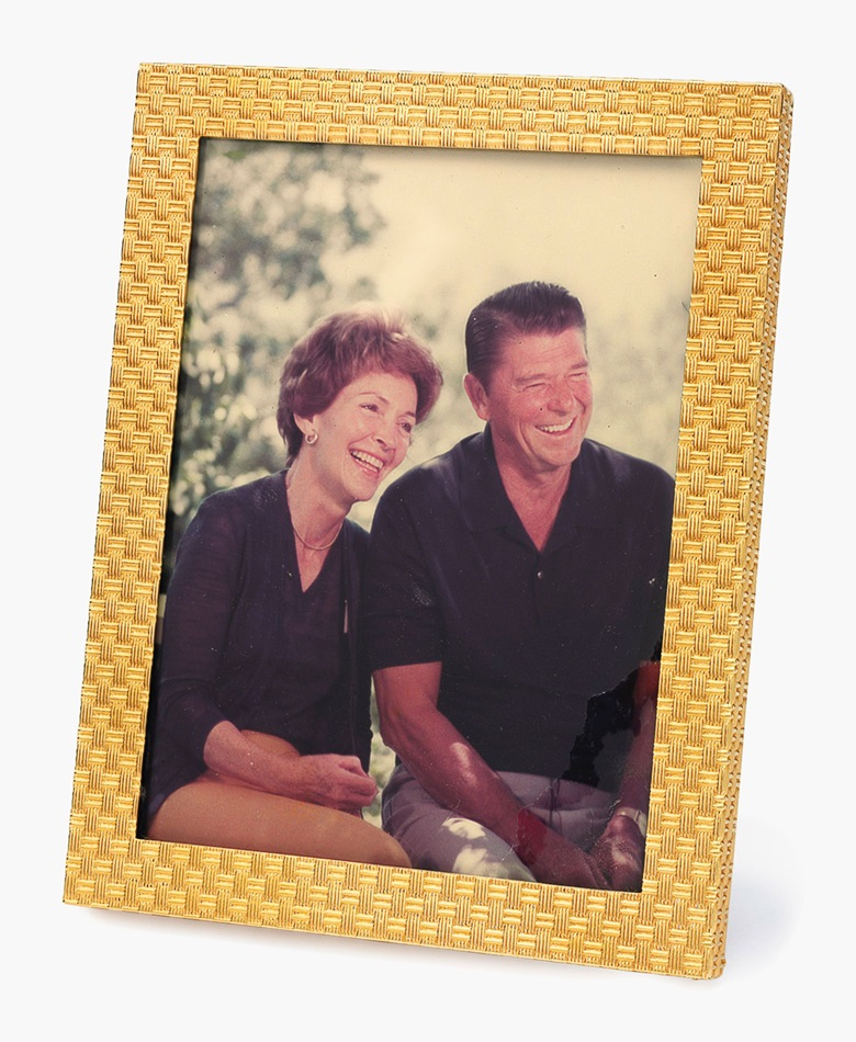 A gold picture frame. The 14k-gold frame of basketweave design, with picture of President and Mrs. Reagan. 4 ½ x 3 ½ ins. This frame was displayed in the White House while President Reagan was in office. Estimate $1,000-1,500. This lot will be offered in The Private Collection of President and Mrs. Ronald Reagan, 21-22 September at Christies in New York