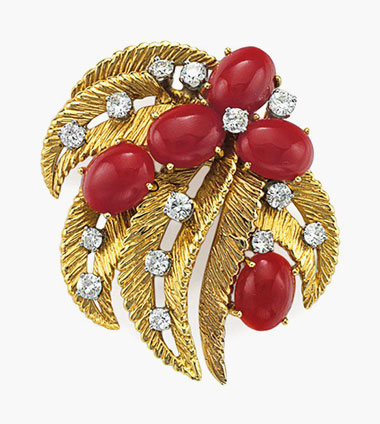 A coral, diamond and gold brooch, by Ruser. Designed as openwork sculpted gold leaves, set with oval cabochon red corals and circular-cut diamonds, mounted in platinum and 18k-gold. Estimate $2,000-3,000. This lot will be offered in The Private Collection of President and Mrs. Ronald Reagan, 21-22 September at Christies in New York