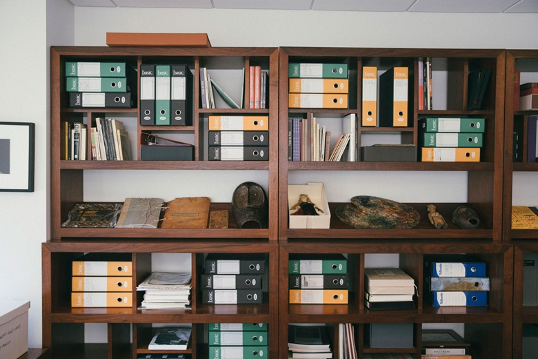 Shelves housing the Amedeo Modigliani archive, which comprises letters, photographs, family documents, and more. The items on display include a painting and sketches created by Modigliani as a child; his travel portfolio, along with a drawing created in Paris; a doll given to by him to his infant daughter Jeanne; African masks presented to him by Paul Guillaume; and his working palette, on which