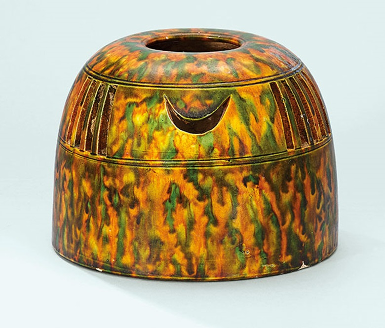 A sancai-glazed hand  warmer. Tang dynasty (618-907). 5⅛ in  (13 cm) high, box. This work was offered in The Pavilion Sale on 4 October 2016 at Christie's Hong Kong and sold for HK$1,000,000$US129,500