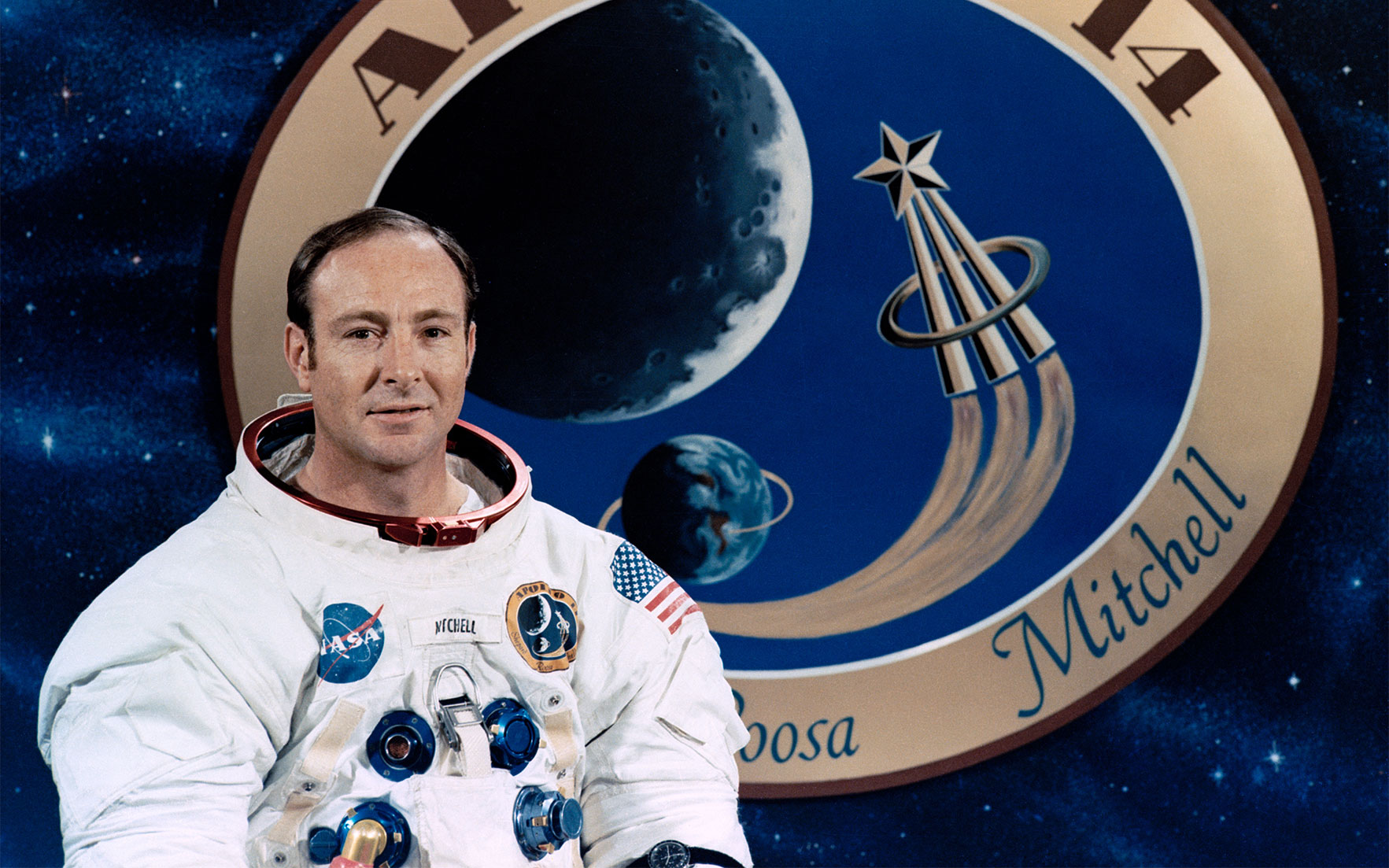 Photograph (detail) of Apollo 14 astronaut Edgar Mitchell in front of a graphic of the mission patch.  Photograph NASA. A copy of the photograph is offered as part of the lot